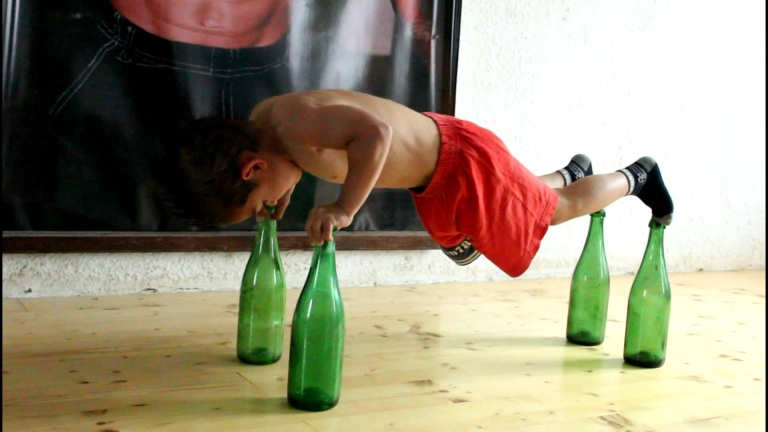 Watch this 5-year-old kid as he does push-up on top of glass bottles