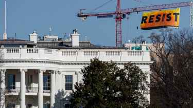 Greenpeace protest Trump by climbing crane near White House and displayed a huge banner that says 'RESIST'